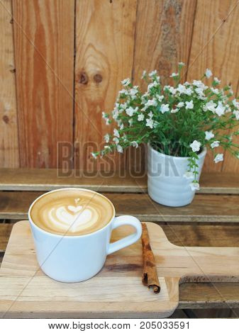 Coffee Cup And A White Fabric Flowers With A Wooden Background. Minimal Style.