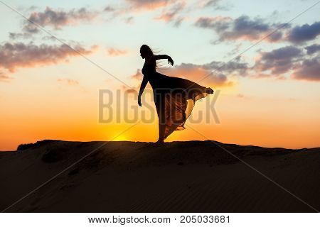 Female dancer dances at sunset her dress is fluttering and translucent. The backlight of the sun only contours of the figures are visible.