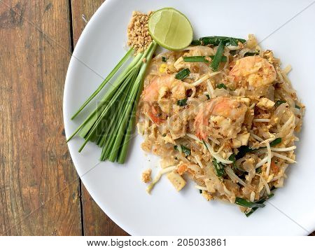 Pad Thai, Stir-fried Rice Noodles With Shrimp In White Plate On Wood Table. The One Of Thailand's Na
