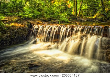 Forest river waterfall. Sun glares on the water