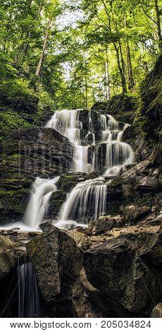 Forest river cascade waterfall. Shepot falls Carpathians