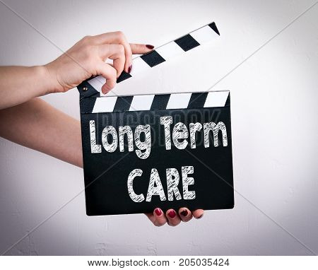 long term care concept. Female hands holding movie clapper.
