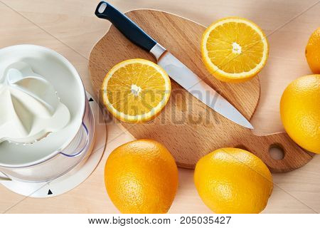 Knife And Oranges On Cutting Board