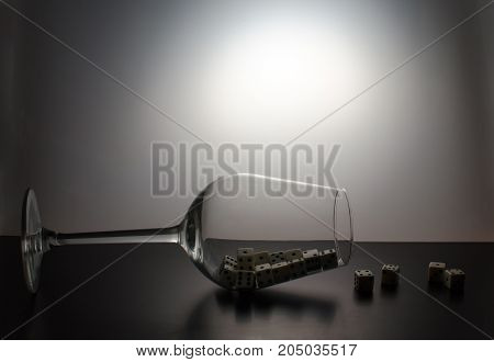 A fallen glass and a scattering of dice on a grey background