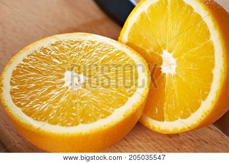 Juicy Bisected Oranges Closeup On Wooden Board