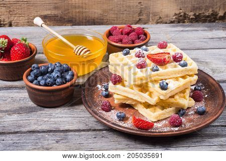 Homemade belgian waffles with berries and honey
