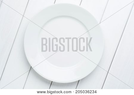 Empty plate on white planked wooden background. Top view with copy space.