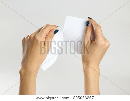 Female Hands Rip A White Sheet Of Paper. Isolated On Gray Background. Closeup