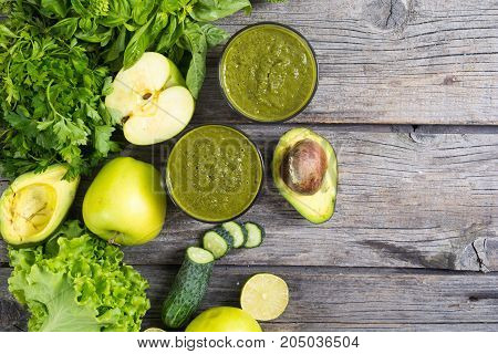 Green detox smoothie in a glass with fruits and vegetables . Top view space for text