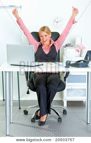 Excited modern business woman sitting at office desk and rejoicing her success