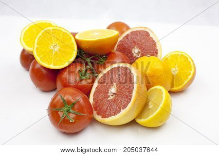 Juicy tomato and orange on the white background with green leafs and droops with copy space