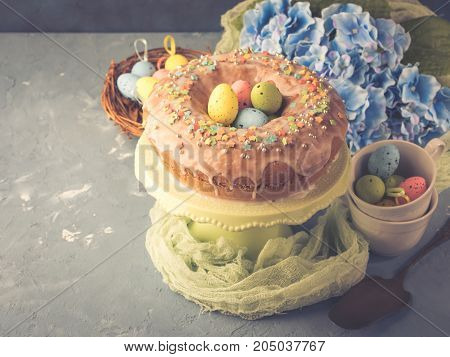 Easter bundt ring cake with sugar frosting sprinkles decorations eggs and hydrangea flowers on blue background. Festive holiday home made sweet food treat. Toned vintage