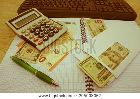 Business Objects in the office on the table calculator and dollars on table. Money and a calculator on the table - Retro color