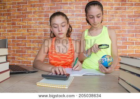 Open book on wooden table. Young girls sitting at desk at home doing homework. Thoughts education creativity concept