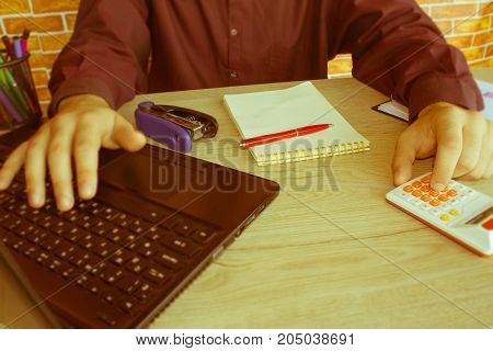 A businessman doing some paperwork using his calculator. man paying bills with his laptop - Retro color