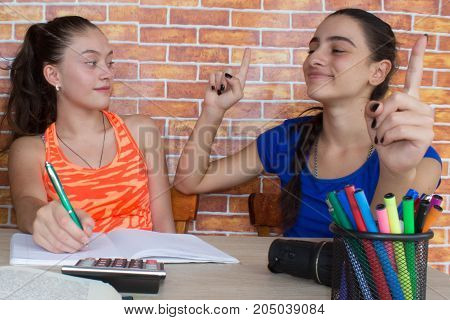 Young girls sitting at desk at home. Two girls sitting at desk at home doing homework. Thoughts education creativity concept