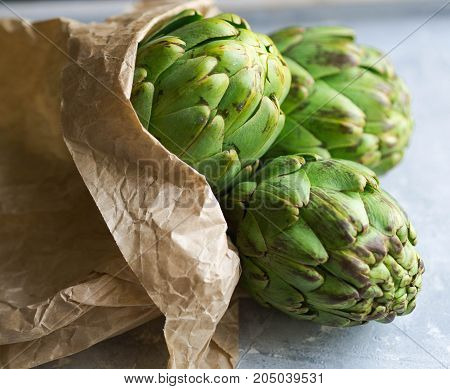 Ripe artichokes in a paper bag on a gray background