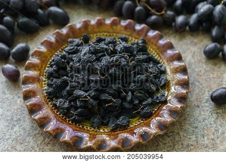 A bunch of fresh sweet dark and succulent raisins poured into a dish grapes lying in a table.
