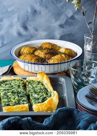 Lunch with spinach quiche and baked potatoes. Winter dinner home made meal