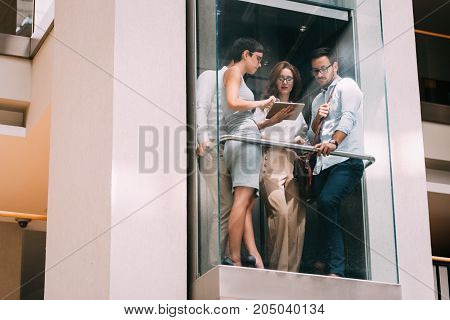 Picture of young attractive businesspeople talking in elevator