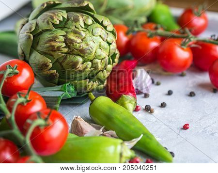 Various red and green vegetables and fruits - chili, artichokes, tomatoes and spices on a gray background. Open space