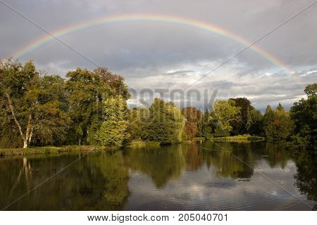 A pond with trees that mirror the surface. Sky with rainbow and clouds before the storm.