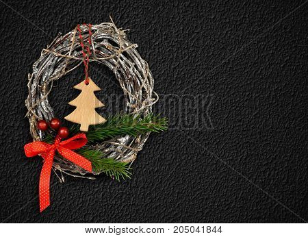 Christmas wreath decoration on black textured stucco wall