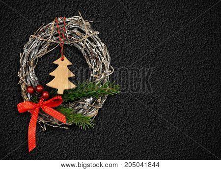 Christmas wreath decoration on black textured stucco wall