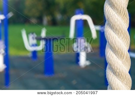 Playground outdoor fitness equipment in the blurred image to the right a fragment of the rope is depicted sharply soft focus.