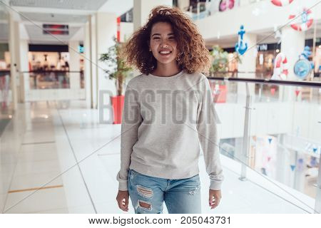 Curly haired girl with freckles in blank grey sweatshirt. Mock up.