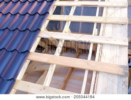Process of metal roof mounting outside house. Wooden house country construction