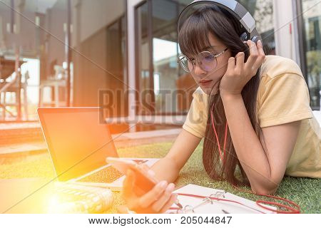 Young Woman Listening To Music With Mobile Phone. Happy Smiling Girl Listening To Music With Earphon