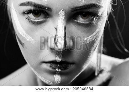 female portrait with professional face art paint cosmetics, monochrome
