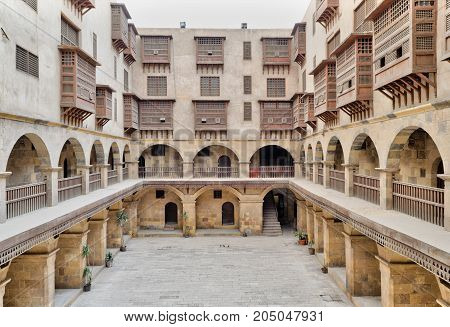 Cairo, Egypt - March 18, 2017: Facade of caravansary (Wikala) of Bazaraa with vaulted arcades and windows covered by interleaved wooden grids (mashrabiyya) suited in Tombakshia street Al Gamalia district Medieval Cairo Egypt