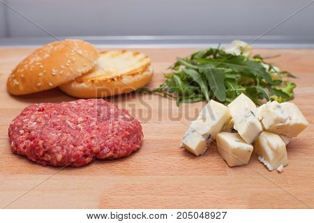 Picture of a cheeseburger before frying meat burger bun gorgonzola cheese and rucola