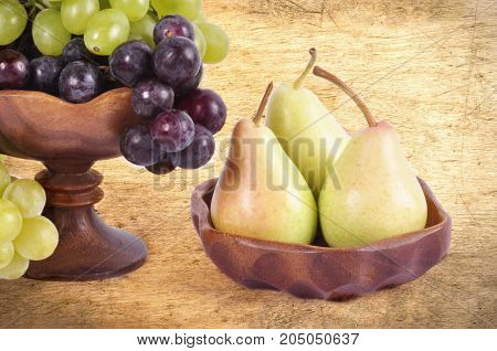 Light and dark grapes in a wooden bowl with an apple pear plum and figs on an abstract background.Fruit still life