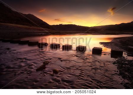 Sunrise over the stepping stones that allow access to the divided beaches at Three Cliffs Bay on the Gower peninsula in Swansea, South Wales, UK
