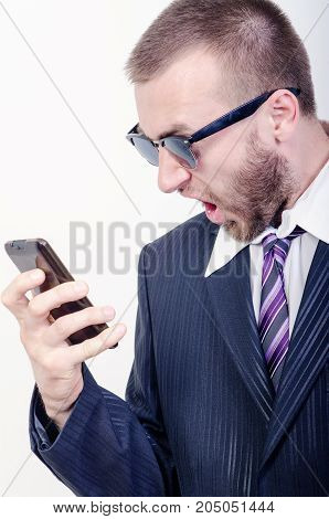 a man in glasses screams into the phone