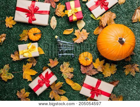 Various Autumn Leaves And Orange Pumpkins Near Shopping Cart
