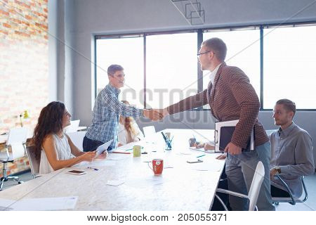 Confident businessman shaking hands with a handsome man on the office background. A successful business meeting with happy workers.