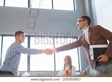 Young executive director shaking hands on a meeting with workers on the office background. Business men shaking hands on a meet-up.