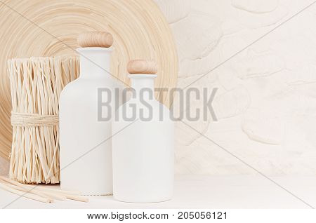 Soft elegant home decor with white bottles and beige twigs on white wooden board. Template for advertising designers branding identity cover.