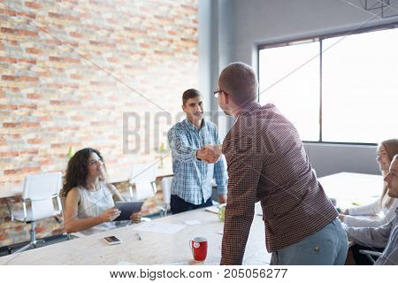 Two young men shaking hands on a successful conference. Young beautiful workers on a meet-up on the office background. Copy space.
