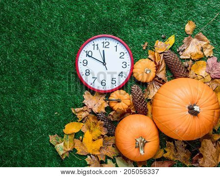 Various Autumn Leaves And Orange Pumpkins With Alarm Clock