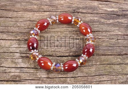Bracelet burgundy color with crystals on the background of an old wooden table