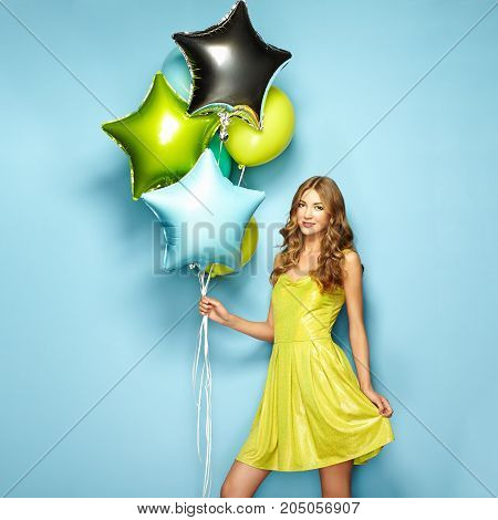 Beautiful young woman with colorful balloons on a blue background. Birthday and party. Girl in green dress at the festival