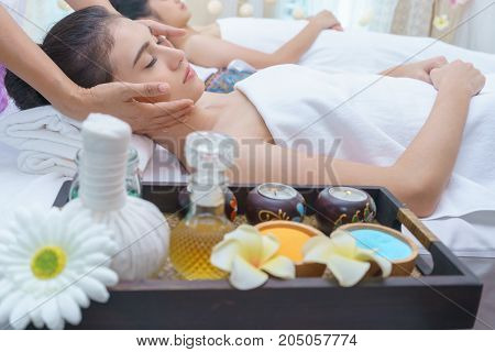 Beautiful young Asian woman relaxing lying on massage table and having Thai traditional face massage in spa salon