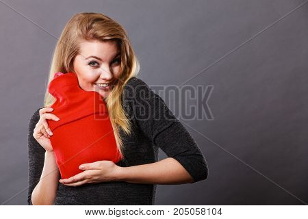 Positive happy woman hugging warm hot water bottle in red soft fleece cover on grey. Health care pain relievers treatment objects concept.