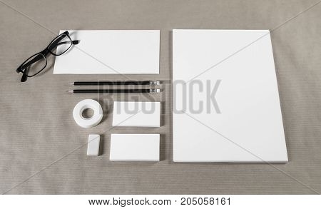 Photo of blank stationery set on paper background. Paperwork template for designers. Responsive design mockup. ID template.