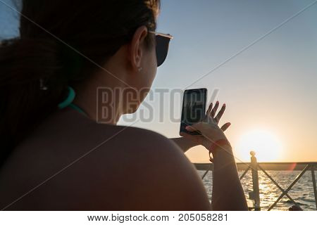 girl is taking pictures of the sunset in a bathing suit background of sea blue water.